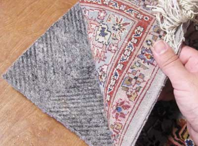 Person is lifting the corner of a rug to show the rug pad underneath.